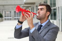Noisy businessman playing a plastic trumpet.  Stock Image