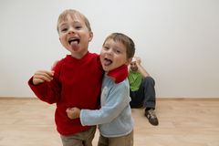 Noisy children annoying adult. Portrait of two noisy children being naughty, with adult in background sat on floor covering his ears stock photos