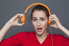 Noisy headphones concept for beautiful 20s girl. Noisy headphones concept - beautiful 20s girl listening to loud music with earphones on,removing her earphones Stock Photos
