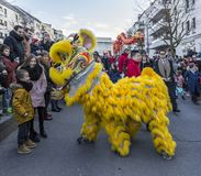 Chinese New Year Parade - The Year of the Dog, 2018. Noisy-le-Grand, France - February 18,2018: The yellow Chinese Lion performing in front of children during royalty free stock photography