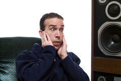Noisy Music. Young Man sitting next to some speakers with his fingers in his ears Stock Image