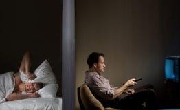 Noisy neighbor. Man at night can't fall asleep because of the noisy neighbor stock photos