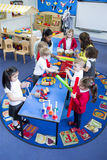 Noisy Nursery Lesson. Nursery children playing with musical instruments in their music lesson with teachers. They are in the classroom stock photography