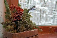 Noite acolhedor do inverno do conceito Ainda vida: ramos e cone coníferos do pinho contra a janela do fundo com árvores cobertos  Imagem de Stock