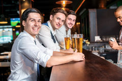 Noite alegre para homens Quatro homens dos amigos que bebem a cerveja e o hav Foto de Stock Royalty Free
