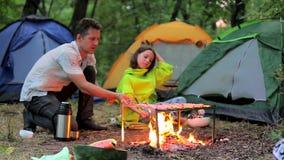Noite atrasada no acampamento, no pai e na filha sentando-se pelo fogo video estoque