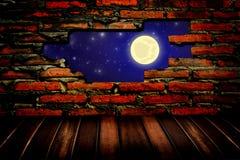 Noite através do furo na parede de tijolo Imagem de Stock