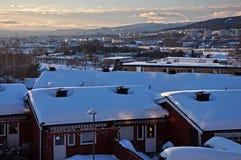 Noite com o sol de ajuste em Oslo nevado imagem de stock