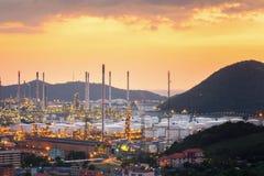 Noite da refinaria de petróleo da opinião de Erial com fundo da montanha durante o crepúsculo, zona industrial Fotos de Stock Royalty Free