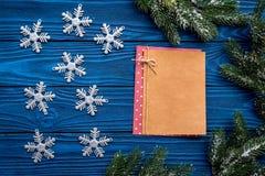 A Noite de Natal ajustou-se com ramos, os flocos de neve e o caderno spruce para definições na zombaria de madeira azul do veiw d Fotografia de Stock