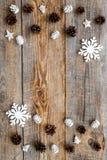 A Noite de Natal com brinquedos do floco de neve e os cones do pinho no fundo de madeira cobrem o modelo do veiw Fotografia de Stock
