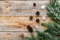 A Noite de Natal com ramos spruce e os cones do pinho no fundo de madeira cobrem o modelo do veiw Fotos de Stock Royalty Free