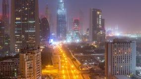 Noite do centro da skyline de Dubai ao timelapse aéreo do dia com tráfego na estrada filme