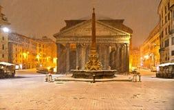 Noite do inverno em Roma com a igreja do blizzard da neve e do templo do panteão no quadrado vazio com luz dourada, Itália imagem de stock