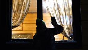 Noite do inverno Em uma sala morna e brilhante perto da janela é um homem novo e bate na janela Tiro fora filme