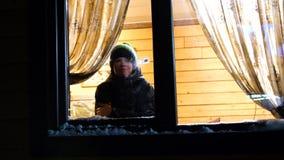 Noite do inverno Em uma sala morna e brilhante perto da janela está um homem novo jogando uma bola de neve na janela filme