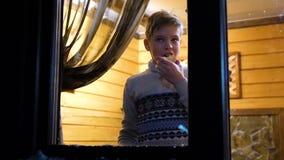 Noite do inverno Em uma sala morna e brilhante perto da janela está um homem novo Tiro fora video estoque