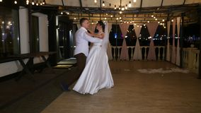 Noite do inverno, um terraço decorado com ampolas, na rua, os recém-casados estão dançando sua primeira dança do casamento filme