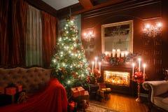 Noite do Natal pela luz de vela apartamentos clássicos com uma chaminé branca, uma árvore decorada, sofá, grandes janelas e Fotografia de Stock