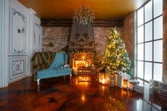Noite do Natal pela luz de vela apartamentos clássicos com uma chaminé branca, uma árvore decorada, sofá, grandes janelas e Fotografia de Stock Royalty Free