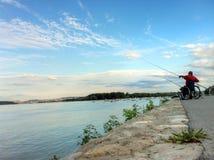 Noite do por do sol em Zemun no rio Danúbio com o pescador na cadeira de rodas imagem de stock