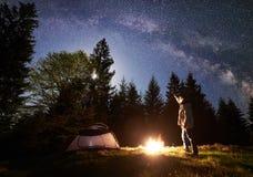 Noite masculina do enjoyng do caminhante que acampa perto da barraca do turista na fogueira sob o céu e a Via Látea estrelados az imagem de stock