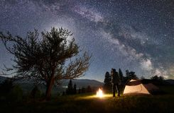 Noite masculina do enjoyng do caminhante que acampa perto da barraca do turista na fogueira sob o céu e a Via Látea estrelados az fotos de stock royalty free