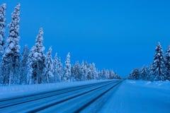Noite na estrada do inverno em Finlandia imagens de stock