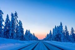 Noite na estrada do inverno em Finlandia imagem de stock