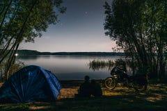 Noite que acampa na costa do lago O homem e a mulher est?o sentando-se Acople os turistas que apreciam surpreendendo a vista do c foto de stock royalty free