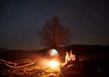 Noite que acampa nas montanhas Acople os caminhantes que têm o resto perto da fogueira, barraca do turista sob o céu estrelado fotografia de stock royalty free