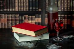 Noite quieta, calma com livros e um vidro do vinho tinto foto de stock