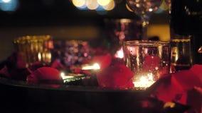 Noite romântica, velas ardentes com pétalas cor-de-rosa vídeos de arquivo
