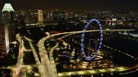 Noite Timelapse da cidade de Singapura com aviador Ferris Wheel With Traffic em torres das construções da estrada e em barcos de  filme