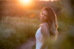 Noiva à moda bonita em uma dança bonita do vestido de casamento em um por do sol Foto de Stock