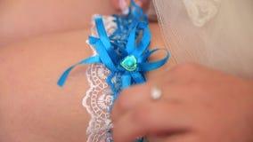 A noiva ajusta uma liga elegante em seu pé video estoque