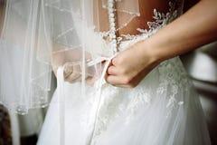 A noiva amarra um vestido de casamento da curva antes da cerimônia de casamento foto de stock royalty free