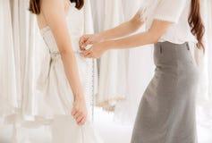A noiva asiática da mulher que tenta no vestido de casamento, mulheres costura a fatura do ajuste com fita de medição, fecha-se a fotografia de stock