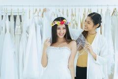 Noiva asiática que tenta no vestido de casamento, desenhista da mulher que faz o ajuste no estúdio da forma foto de stock royalty free