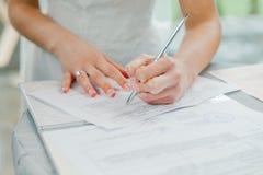 A noiva assina os originais do registro de união Originais de assinatura do casamento dos pares novos Imagens de Stock