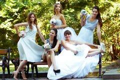 A noiva aumenta seus pés acima ao descansar com as damas de honra ser Imagem de Stock Royalty Free
