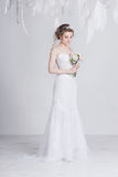 A noiva bonita com laço floresce em seu cabelo louro escuro lindo Penteado, tranças e ondas altos do casamento imagem de stock royalty free