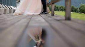 A noiva bonita com o noivo no fundo das montanhas é refletida na água O conceito de um feliz filme