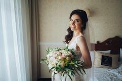Noiva bonita com um ramalhete das flores na sala de hotel Imagem de Stock Royalty Free
