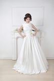 Noiva bonita da forma no vestido luxuoso do casamento que levanta agains imagem de stock