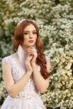 Noiva bonita do ruivo no vestido de casamento fantástico no jardim de florescência imagens de stock