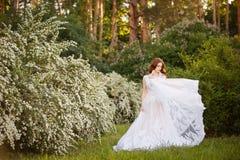 Noiva bonita do ruivo no vestido de casamento fantástico no jardim de florescência fotos de stock royalty free