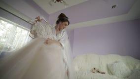 A noiva bonita e bonita no vestido da noite guarda o gancho com um vestido de casamento Manhã do casamento Mulher bonita e bem ar filme