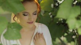 Noiva bonita e bonita no vestido da noite e v?u no jardim Manh? do casamento filme
