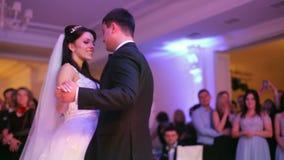 Noiva bonita e noivo considerável que dançam primeiramente a dança no banquete de casamento filme